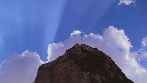 Time lapse of clouds and sun rays over strange tow Stock Video Footage