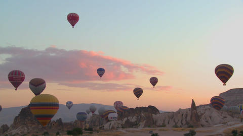 Hot air ballons rise from the desert floor against Footage