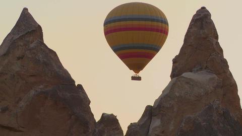 A hot air balloon flies through a narrow canyon in Footage