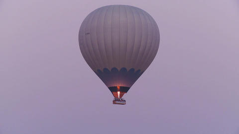 A hot air balloon flies against a purple sky Stock Video Footage