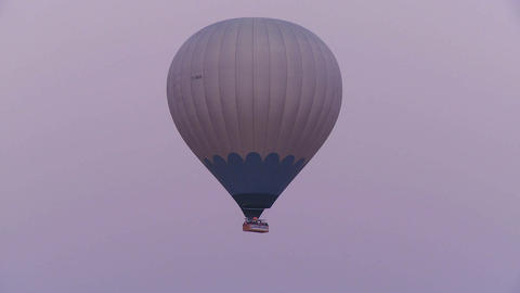 A hot air balloon flies against a purple sky Footage