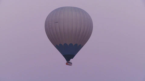 A hot air balloon flies against a purple sky Stock Video Footage