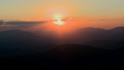 Medium-shot of a fiery sunset over a generic mount Stock Video Footage