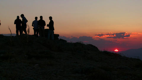 People stand in silhouette at sunrise of sunset on Stock Video Footage