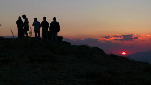 People stand in silhouette at sunrise of sunset on Footage