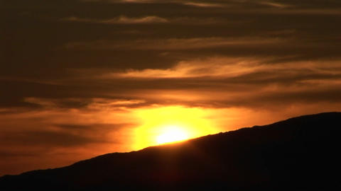 A golden sun sinks behind a silhouetted mountain Stock Video Footage