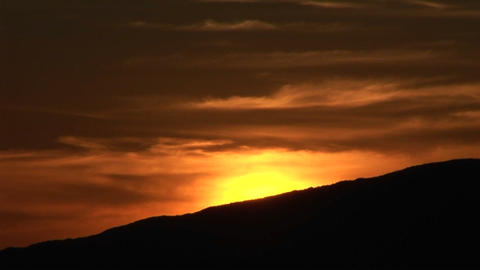 A golden sun sinks behind a silhouetted mountain Footage