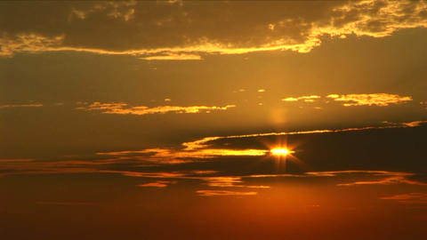 A golden sun peeks through a bank of clouds Stock Video Footage