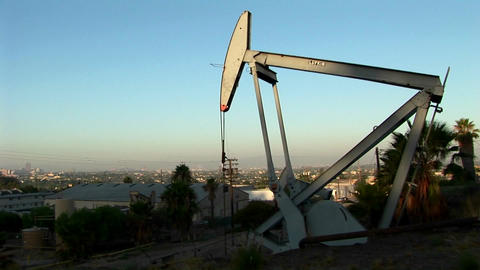 An oil well pumps at dawn with a sprawling suburban landscape behind Footage