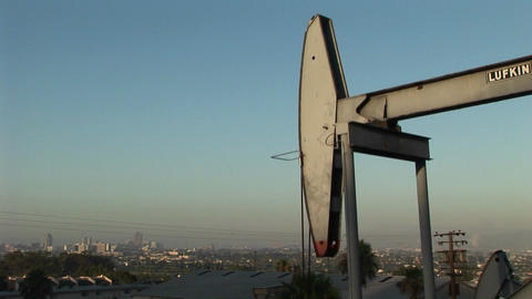 An oil well pumps oil with a sprawling suburban landscape... Stock Video Footage