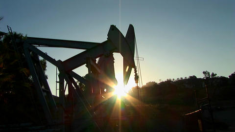A pump jack is silhouetted against the sun Footage