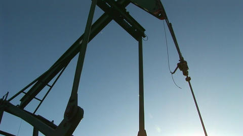 A pump jack is silhouetted against a blue sky Stock Video Footage