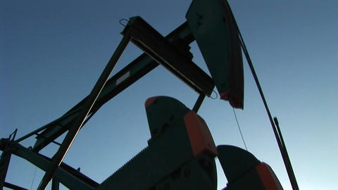 A pump jack is silhouetted against a blue sky Footage