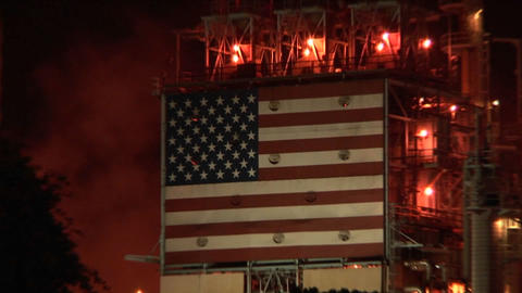 An American flag mural decorates the side of an oil refinery at night Footage