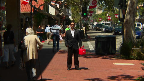 A man holds a gas can as pedestrians and traffic move... Stock Video Footage