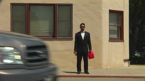 A man holding a gas can stands on a sidewalk with traffic... Stock Video Footage