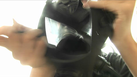 A man wearing a gas mask and other protective gear places... Stock Video Footage