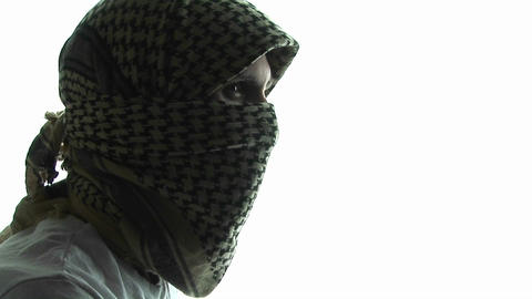 A terrorist wearing a mask turns away from the camera Stock Video Footage