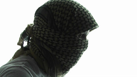 A terrorist, in profile, wears a kaffiyeh scarf Footage