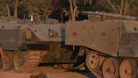 Israeli armored vehicles sit parked in the desert Footage
