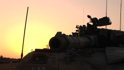 An Israeli tank is silhouetted against a multi colored sky Stock Video Footage