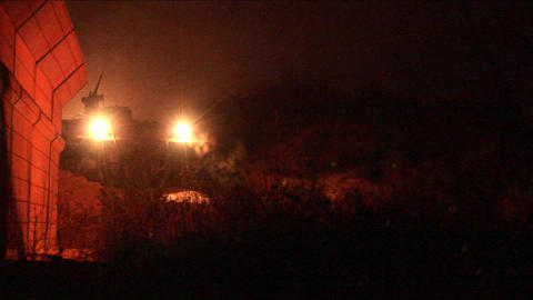 An Israeli army tank patrols along the border wall at night Stock Video Footage