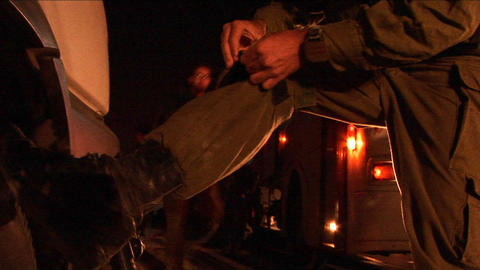 An Israeli soldier adjusts his boots during a night... Stock Video Footage