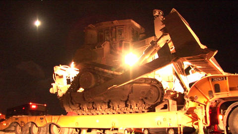 An Israeli armored bulldozer is unloaded from a flatbed truck for night patrol along the Gaza Strip Footage