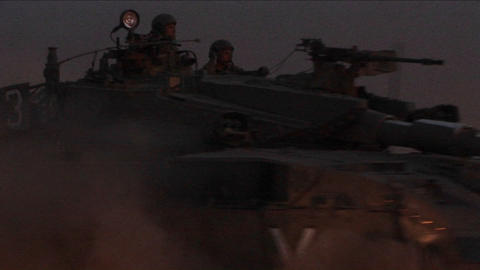 An Israeli tank passes at high speed during an early morning patrol on the Gaza or Lebanon border Footage