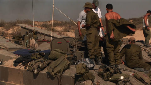 Off duty Israeli soldiers stand on top of a tank during a conflict in a border region Footage