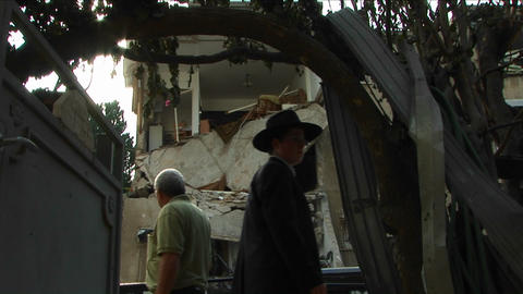 Pedestrians in Haifa pass by an apartment building destroyed by a rocket attack Footage