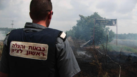 An Israeli police officer looks on as fire spreads from a... Stock Video Footage