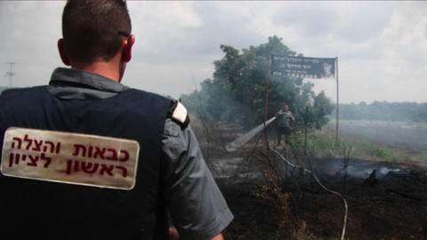 An Israeli police officer looks on as fire spreads from a rocket attack in Northern Israel Footage