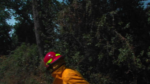 A firefighter walks quickly down a dirt road approaching... Stock Video Footage