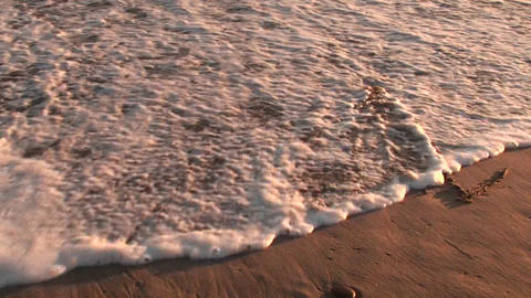 "An ocean wave washes over EROSION"" written in the sand Stock Video Footage"