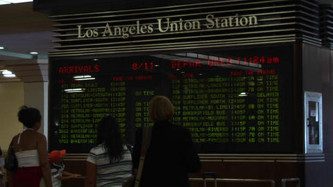 Passengers look at train arrivals and departures at the... Stock Video Footage