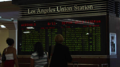 Passengers look at train arrivals and departures at the Los Angeles Union Station Footage
