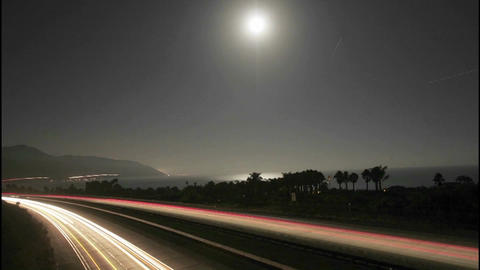 Time lapse of the moon and traffic near the beach at night Stock Video Footage