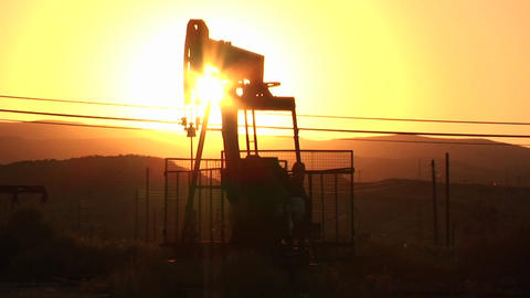 An oil derrick pumps at sunset Stock Video Footage