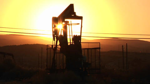 An oil derrick pumps at sunset Footage