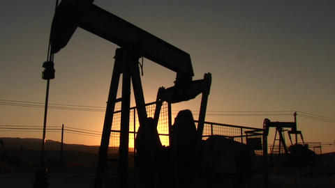 Oil derricks pump at sunset Footage