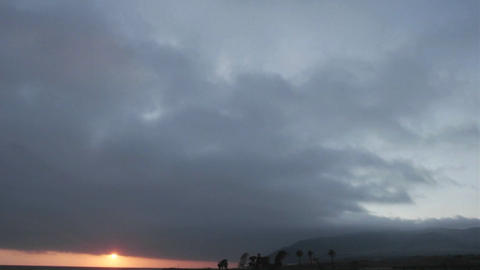 Time lapse of dark clouds and the sun setting Live Action