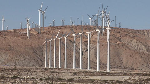 Many windmills on a hillside rotate in a breeze Stock Video Footage