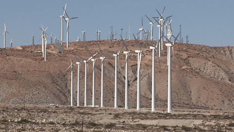 Many windmills on a hillside rotate in a breeze Footage