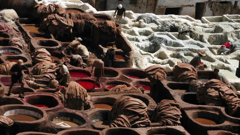 A time lapse of people dying clothes in large clay vats Stock Video Footage