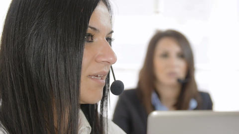 two female operators at work in a help desk center. Call center, customer care Live Action