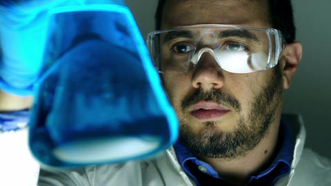 scientist at work with a glass beaker and chemical substances Footage