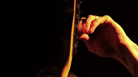 musician tunes a guitar during a concert Footage