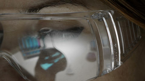 woman working in a chemical lab, detail on spectacles Live Action