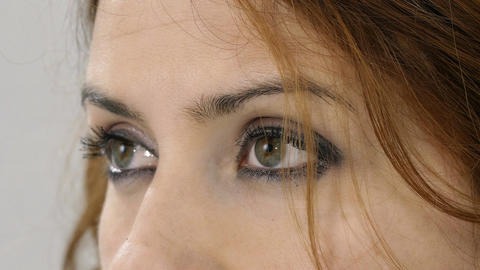 detail of white young woman opening her eyes and glancing Footage
